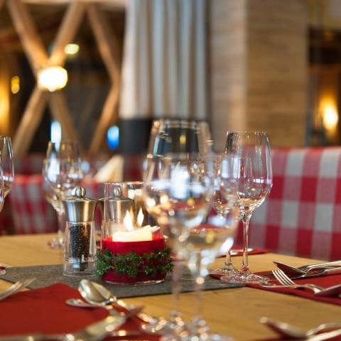 Gedeckter Tisch mit Weingläsern und brennender Kerze